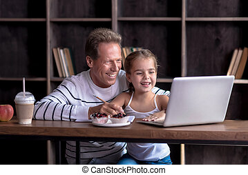 Girl drawing in front of the computer with her grandfather