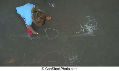 Girl drawing on asphalt - Little girl using chalk to draw on...