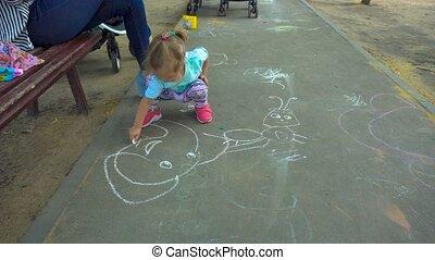 Girl drawing on asphalt near mother - Lovely little girl...