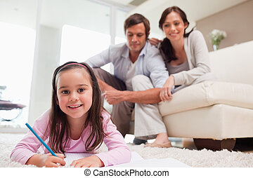 Girl drawing with her parents in the background