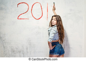 Girl draws a Christmas decoration on the wall.