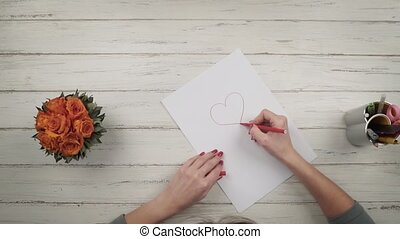 Girl draws a heart on a white sheet of paper. Top view. Hands close up view