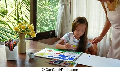 Girl draws a picture with pencils. Mother hugs and kisses child