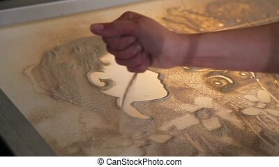 Girl draws boy's face with sand