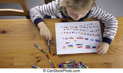 Girl draws flags with colored pencils