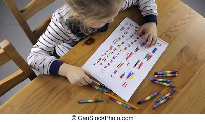 Girl draws flags with pencils