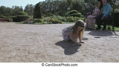 Girl draws in the sand