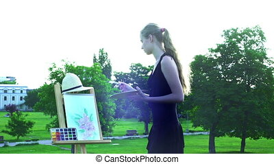 Girl draws on plein air on green grass in city park - Girl...