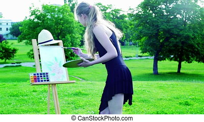 Girl draws on plein air on green grass in park - Girl draws...