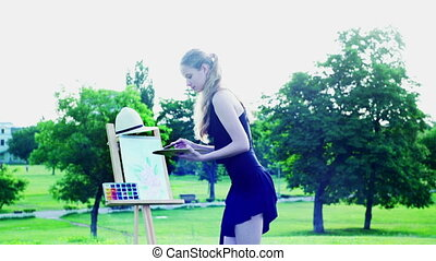 Girl draws on plein green grass and tree in park - Girl...