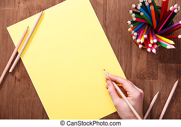 Girl draws with colored pencils on yellow paper on the wooden table. Mockup