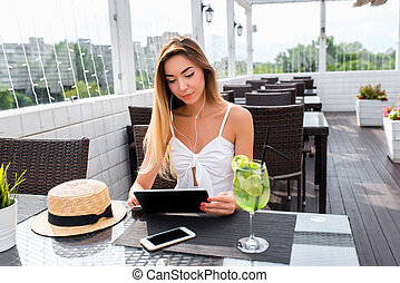 Girl dress headphones sits in summer cafe. In hands of tablet on table phone, glass of lime green. Listening to music, watching a video. Social networking application. Worldwide connection interface
