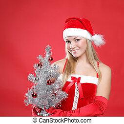 Girl dressed as Santa and a christmas fur-tree