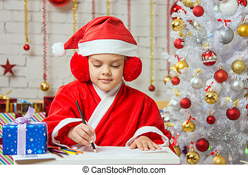 Girl dressed as Santa Claus writing on a sheet of paper sitting at the table