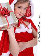 Girl dressed in a Santa costume holding aloft a present