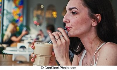 Girl drink latte coffe from straw profile side view