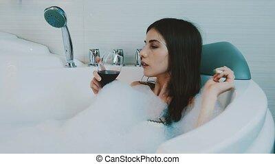 Girl drink red wine in bath full of foam. Smoking electronic cigarette. Bathroom