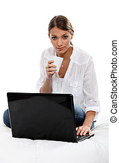 Girl drinking a tea in front of laptop