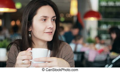 girl drinking coffee and talking to someone