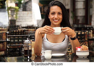 Girl drinking coffee at cafe - Attractive girl in bistro...