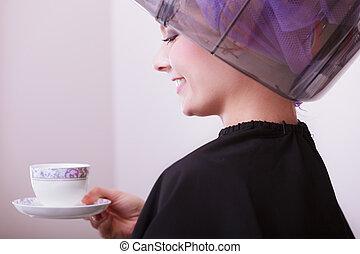 Girl drinking coffee in hair salon