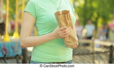 girl drinking from a paper bag in the street. anti-social...