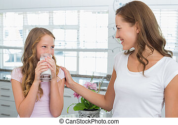 Girl drinking milk as she looks to her mother in kitchen