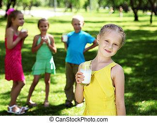 Girl drinking milk in the summer park