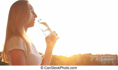 Girl drinking mineral water at sunset. Slow Motion.