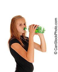 Girl drinking pop from bottle.