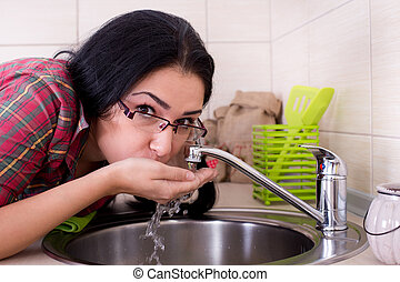 Girl drinking tap water - Young beautiful girl with glasses...
