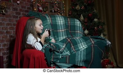 Girl drinking tea and having fun in a chair near a Christmas tree