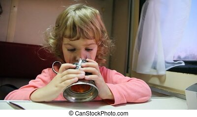 girl drinking tea from glass with glass holder in coach -...