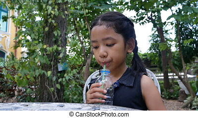 Girl drinking water in the garden