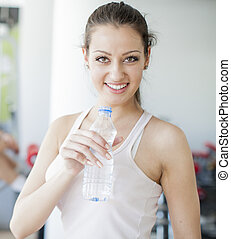 Girl drinking water in the gym