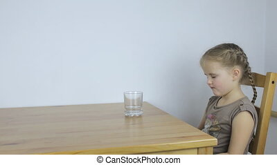 Girl drinks a tablet with water while sitting at the table