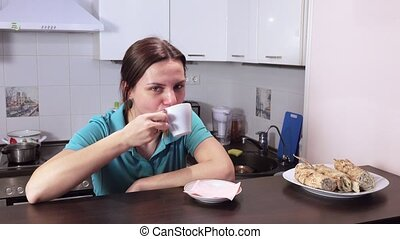 Girl drinks coffee and watches TV - With a coffee standing...