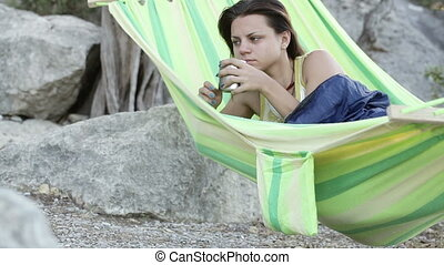 Girl drinks coffee in hammock