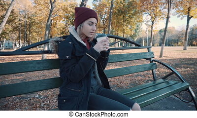 Girl drinks coffee on a bench in the Park. Girl in a jacket and hat