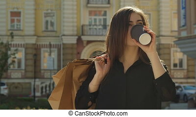 Girl drinks coffee on the street