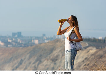 Girl drinks from a bottle of water, standing against the backdrop of a mountain and city landscape