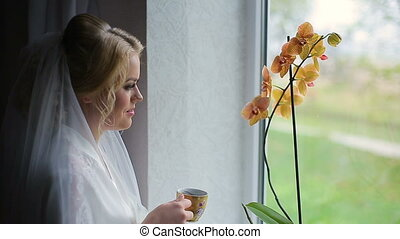 Girl drinks from a mug near window close up
