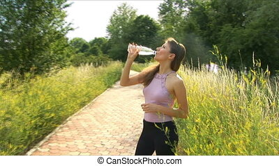 Girl drinks water after playing sports