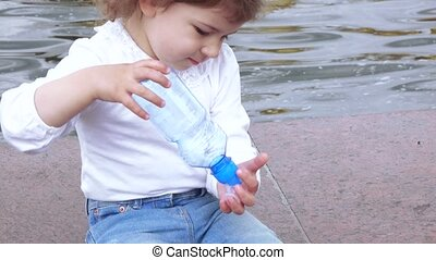 Girl drinks water from the bottle