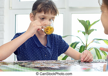 Girl drinks water playing board games at the table