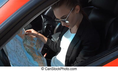girl driver sits behind the wheel of a car and looking map