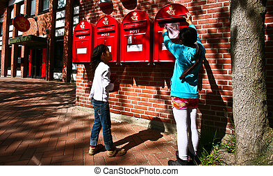 girl dropping a letter in a red postbox in denmark