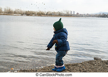Girl dropping stones into the river