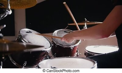 Girl drummer takes turns beats on each drum, close up