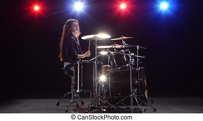 Girl drummer with chopsticks beats rhythmic music. Black background . Red light blue. Side view